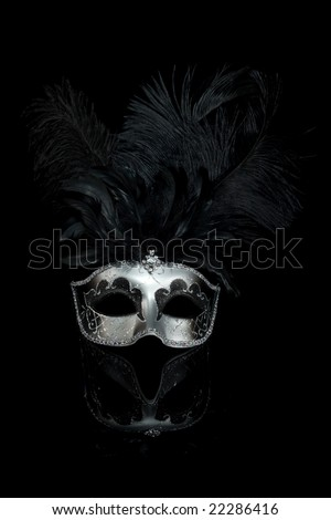 Black silver venetian carnival mask with feathers isolated on black background - stock photo