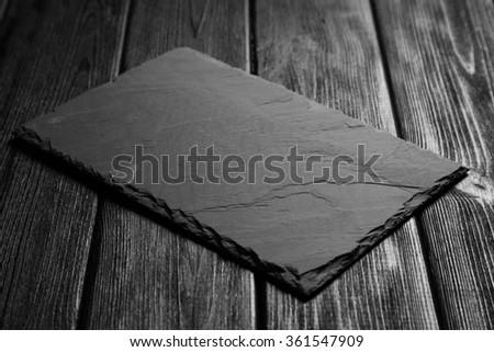 Black slateboard on dark wood - stock photo