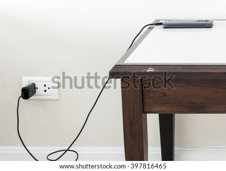 Black smart phone is charging with wall outlet on the wooden table,Select focus - stock photo