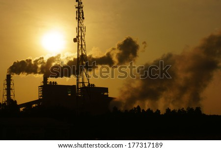 Black smoke from smoke stack of factory in industrial zone rose in to the air, it make polluted enviroment, the plant in silhouette at sunrise, atmosphere cover with waste exhaust - stock photo