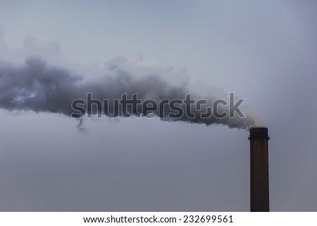 Black smoke spewed from coal powered plant smoke stacks - stock photo