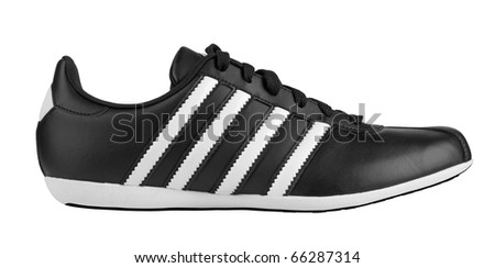 Black sneaker with white strips isolated on white background - stock photo