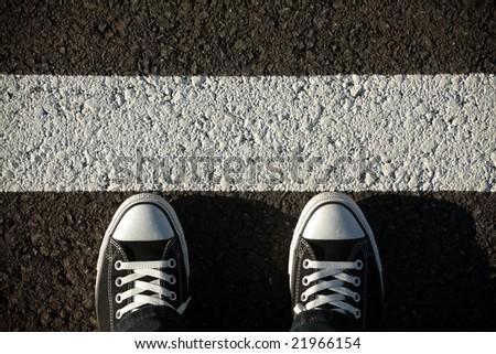 Black sneakers on asphalt, top view - stock photo