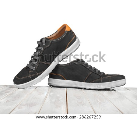 black sneakers on white wooden white background - stock photo