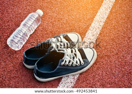 Black sneakers with water bottle on stadium background
