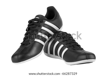 Black sneakers with white strips isolated on white background - stock photo