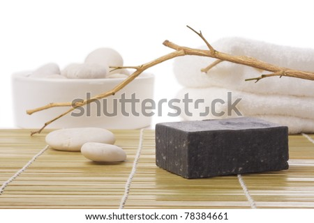 black soap on bamboo mat with stone and towel - stock photo