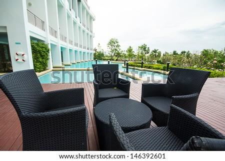 Black sofa set put near outdoor pool. - stock photo