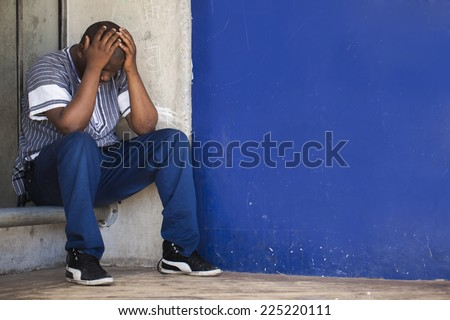 Black South African man sitting in a corner to depict depression and stress that men are suffering from in Africa. - stock photo