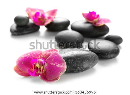 Black spa stones and orchids isolated on white - stock photo
