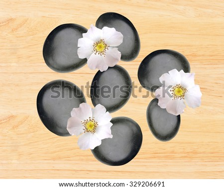 Black spa stones and white spring flowers over yellow wooden background - stock photo