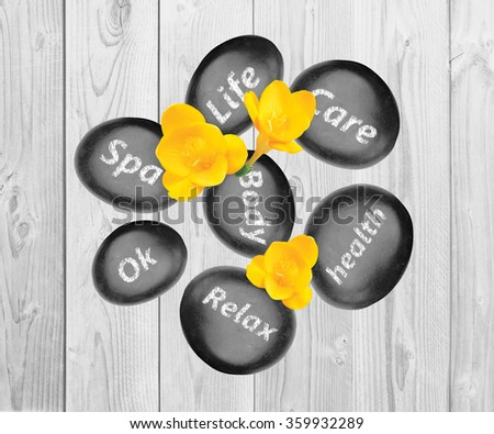 Black spa stones and yellow freesia flowers on wooden background - stock photo