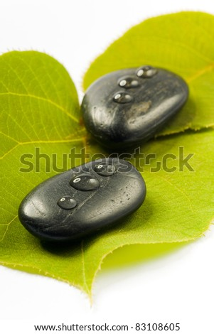 black spa stones with drops on a green leaf on white ground - stock photo
