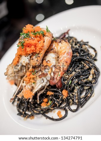 Black spaghetti with prawn in white plate isolated