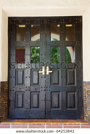 Black Spanish style double doors with tile and stucco walls - stock photo