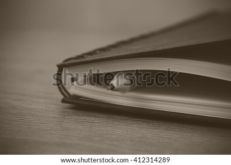 Black spiral bound notebook with pen on wooden background. Black and white filter applied.