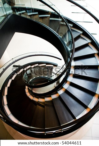 black spiral staircase in restaurant with shiny wooden handrail. - stock photo