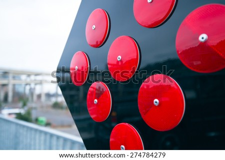 Black square with fixed on it round red reflectors folded up the ranks as a road sign directing information and warning to drivers of vehicles entering the zone of influence of a road sign. - stock photo