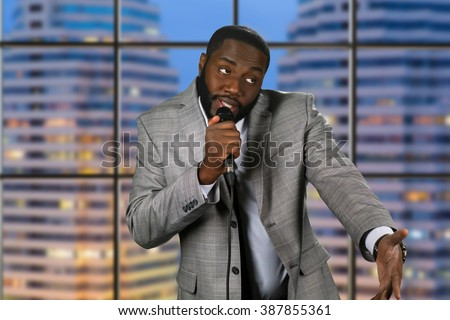 Black stand-up comedian. Evening comedy show on television. Comedian on urban background. Telling jokes on stage. - stock photo