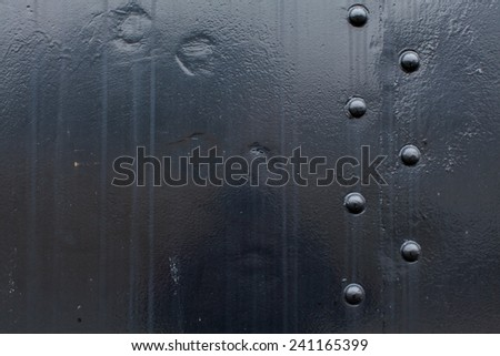 Black steel metal with water erosion, rivet screws, indention and white and brown specks of paint - stock photo