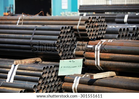 Black steel pipe bundle in industrial stockyard.
