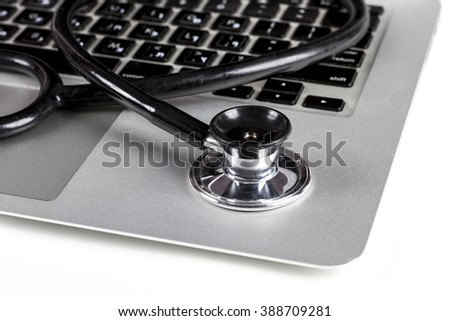 Black Stethoscope Closeup On Silver Laptop  With White Background - stock photo