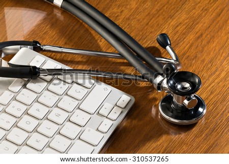 Black stethoscope lying on computer keyboard - stock photo