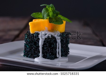 Black sticky rice dessert, thai art, with mango coconut milk and mint leaves as decoration on white plate.