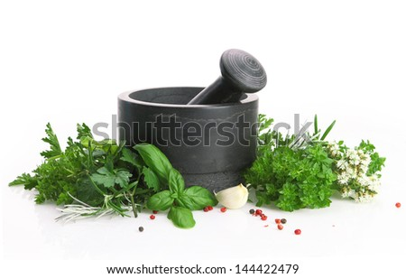 Black stone mortar and pestle with fresh herbs - stock photo
