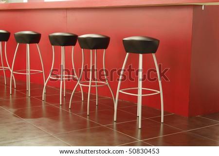 Black stool in interior of bar on ceramic floor - stock photo