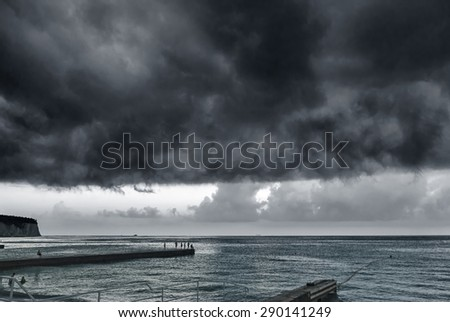 Black storm clouds hung over the sea
