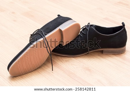 Black suede shoes with laces on a background of wooden parquet