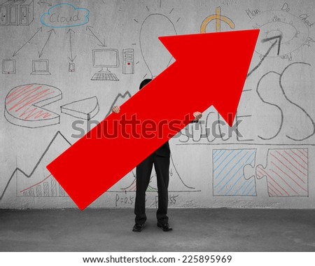 black suit businessman holding red arrow sign on concrete floor with doodles wall - stock photo