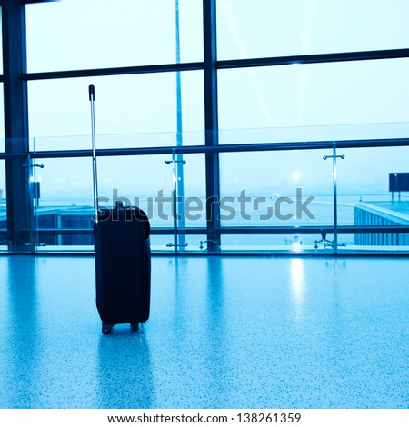 Black suitcase in the airport lounge. - stock photo