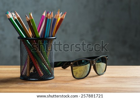 Black sun glasses with bunch of color pencils in a stand - stock photo