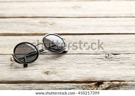 Black sunglasses on a grey wooden table