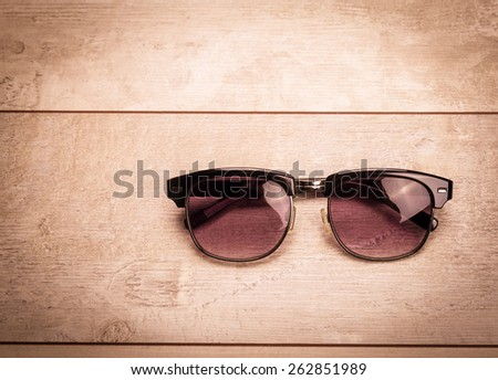 black sunglasses on wood floor - stock photo