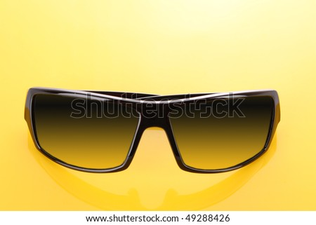 Black sunglasses on yellow  background - stock photo