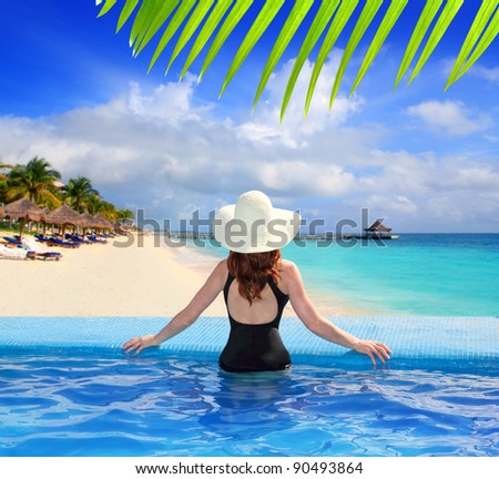 black swimsuit woman rear view in a pool with direct view to tropical Caribbean sea [ photo-illustration] - stock photo