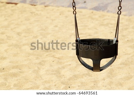 Black swing on the children's playground with sand as a background on sunny day