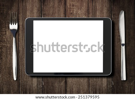 black tablet pc or ipad on dark wooden table with fork and knife - stock photo