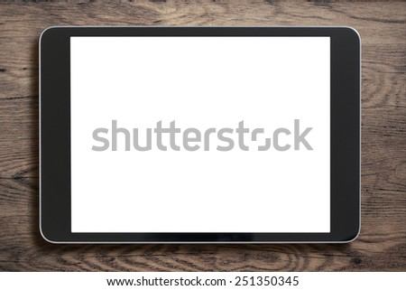 Black tablet pc that looks like ipad mini on old wood background - stock photo