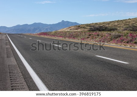 Black tarred two-lane road with white and yellow stripes/Asphalt Paved Surface of Dual-Lane Highway with White and Yellow Markings/Blacktop two-lane road with white and yellow stripes - stock photo