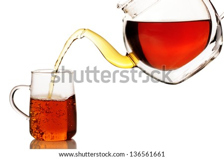 Black tea being poured into a cup off a thermo teapot, isolated on white - stock photo
