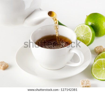 Black tea being poured into tea cup - stock photo