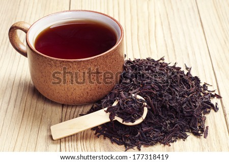 Black tea in a cup and dried leaves on wooden background - stock photo