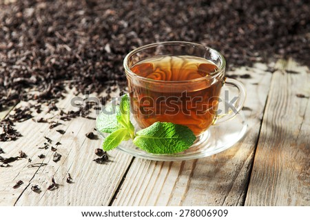 Black tea in a glass cup and saucer on a wooden table. Next to a cup of black tea scattered dry tea  - stock photo