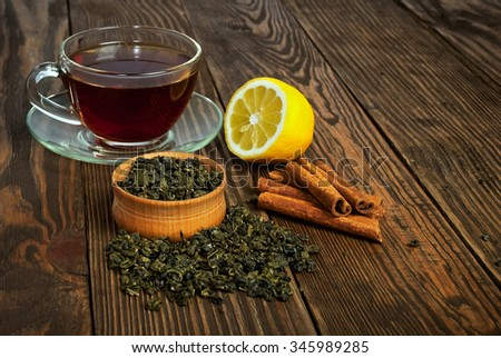 Black tea in cup of glass, lemon and cinnamon on an old wooden table - stock photo