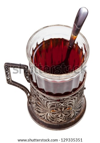 black tea in vintage glass with teaspoon isolated on white background