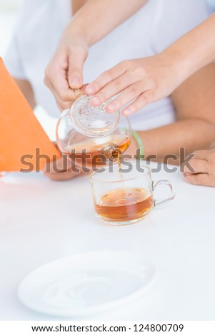 Black tea is poured into a cup